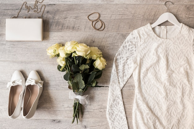 Abendschuhe; kupplung; haarband; rosenstrauß und hochzeitskleid auf hölzernem hintergrund Kostenlose Fotos