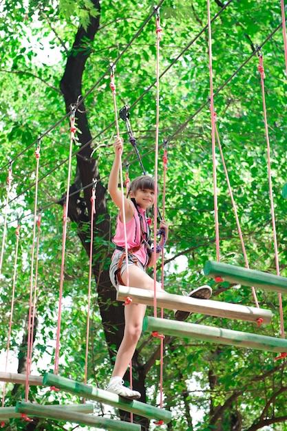 Abenteuer klettern hochseilgarten - wandern im seilpark mädchen. Premium Fotos