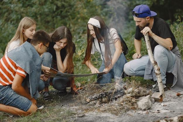 Abenteuer-, reise-, tourismus-, wander- und personenkonzept. gruppe lächelnder freunde in einem wald. leute sitzen in der nähe von lagerfeuer. Kostenlose Fotos