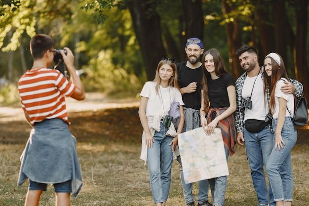 Abenteuer-, wander- und personenkonzept. gruppe lächelnder freunde in einem wald. guy macht ein foto. Kostenlose Fotos