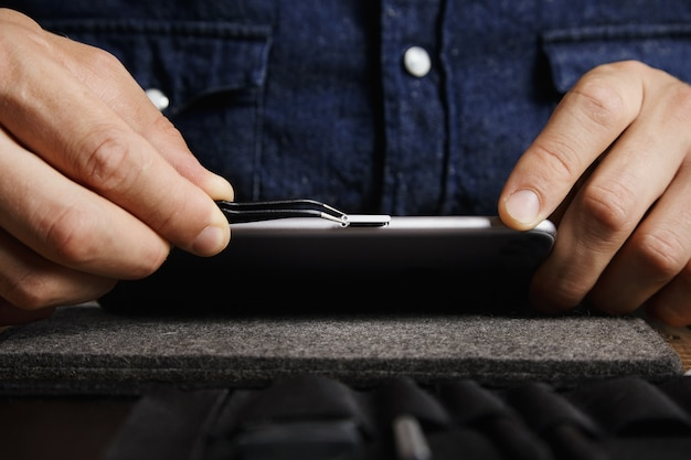 Abgewinkelte esd-pinzette, die das micro-sim-kartenfach aus dem körper des mobilen smartphones in der nähe der toolkit-tasche herauszieht Kostenlose Fotos