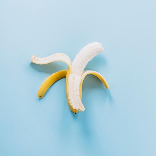 Abgezogene banane auf blauem hintergrund Kostenlose Fotos