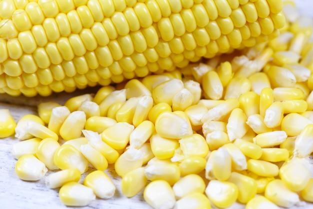 Abgezogene kornähre - frische maissamen auf weißem hölzernem hintergrund Premium Fotos