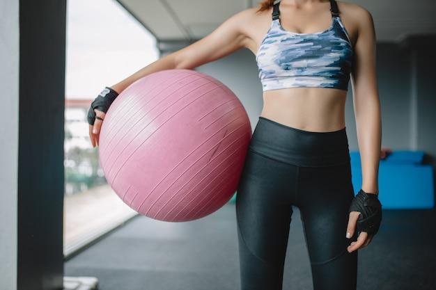 Abschluss herauf asiatisches frauenmodell hält yogaball an der turnhalle, die für übung, übungsmädchen sich vorbereitet Premium Fotos