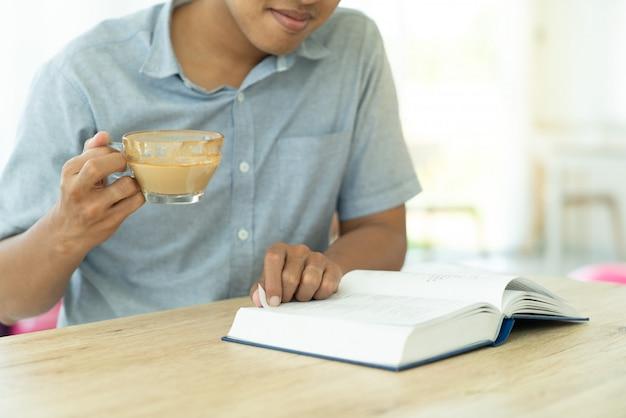 Abschluss herauf den jungen mann, der ein buch für zunahmewissensbildung während liest, haben ein coffe im café Premium Fotos