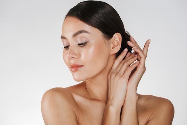 Abschluss oben der entspannten brunettefrau mit der sauberen haut, die an der kamera mit den geschlossenen augen, getrennt über weiß aufwirft Kostenlose Fotos
