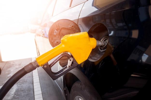 Abschluss oben des autos füllt ölkraftstoff in der tankstelle wieder Premium Fotos