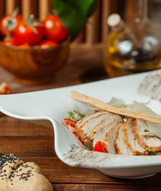 Abschluss oben des caesar-salats mit gegrillten hühnerscheiben, parmesankäse und breadstick Kostenlose Fotos