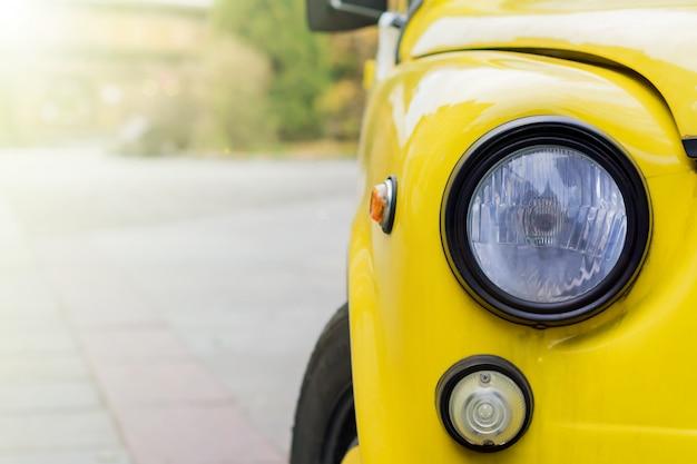 Abschluss oben des gelben retro- autos mit runden scheinwerfern. Premium Fotos