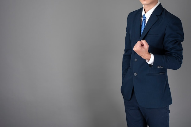 Abschluss oben des geschäftsmannes im blauen anzug ist im grauen hintergrund erfolgreich Premium Fotos