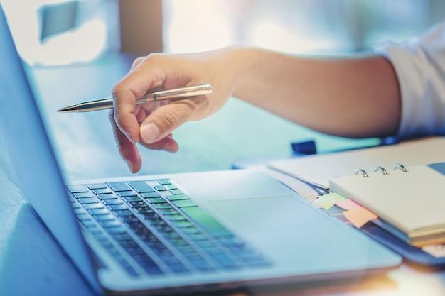Abschluss oben des geschäftsmannfingerdrucks tragen knopf auf laptop-computer ein Premium Fotos