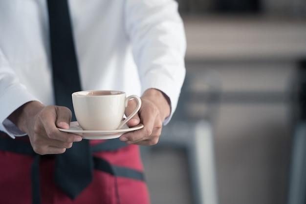 Abschluss oben des kellners, der einen tasse kaffee im café dient. Premium Fotos