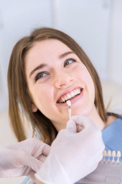 Abschluss oben des zahnarztes mit zahnfarbproben, die schatten für weibliche geduldige zähne wählen Kostenlose Fotos