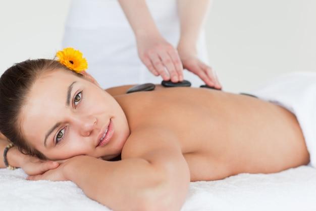 Abschluss oben einer begeisterten frau, die eine heiße steinmassage hat Premium Fotos