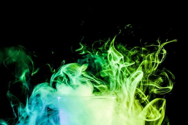 Abschluss oben eines transparenten glases, das mit einer wolke von einem grünen vape gefüllt wird, raucht und steht auf einem schwarzen getrennten hintergrund Premium Fotos