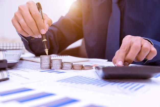 Abschluss oben, hand, die geldmünzenstapel in das sparen des geldes und in wachsendes geschäftskonzept einsetzt. Premium Fotos