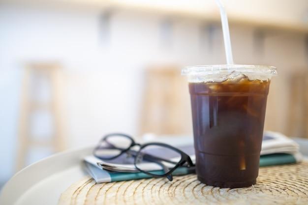Abschluss oben von nehmen plastikschale gefrorenen schwarzen kaffee americano auf rundtisch weg Premium Fotos