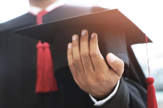 Abschluss, student hält hüte in der hand bei studienbeginn erfolg absolventen der universität Premium Fotos