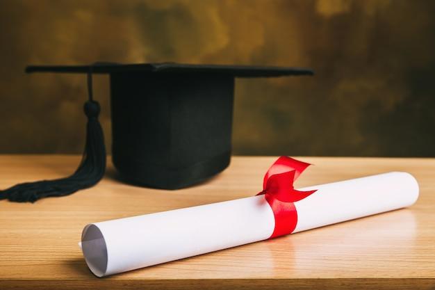 Abschlusskonzept graduationskappe, hut mit diplompapier auf hölzerner tabelle. Premium Fotos