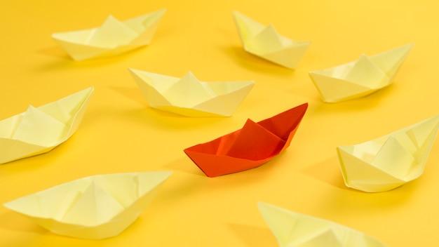 Abstrakte anordnung mit papierbooten auf gelbem hintergrund Kostenlose Fotos