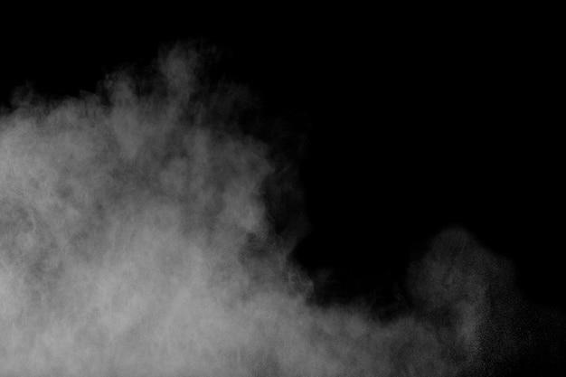 Abstrakte explosion des weißen pulvers gegen schwarzen hintergrund. abstrakter weißer staub atmen aus. Premium Fotos