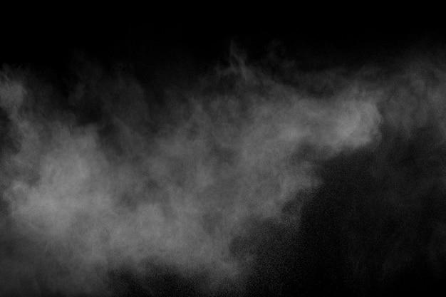 Abstrakte explosion des weißen pulvers gegen schwarzen hintergrund n weißer staub atmen in der luft aus. Premium Fotos