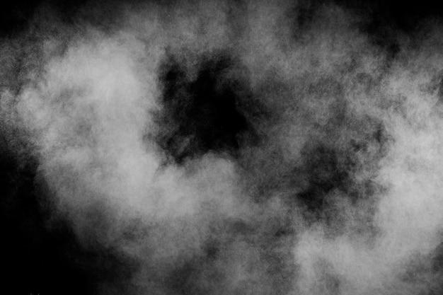 Abstrakte explosion des weißen pulvers gegen schwarzen hintergrund. weiße staubwolke in der luft. Premium Fotos