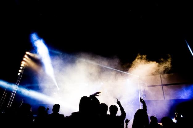 Abstrakte konzertparty silhoue mit licht und rauch im glücklichen moment Premium Fotos