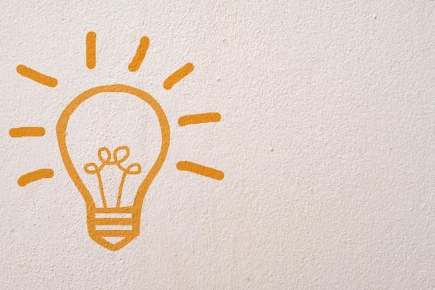 Abstrakte orange denkende glühlampe auf betonmauerhintergrund Premium Fotos