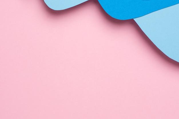 Abstrakte papierschnittblauwellenkunst auf rosa Premium Fotos