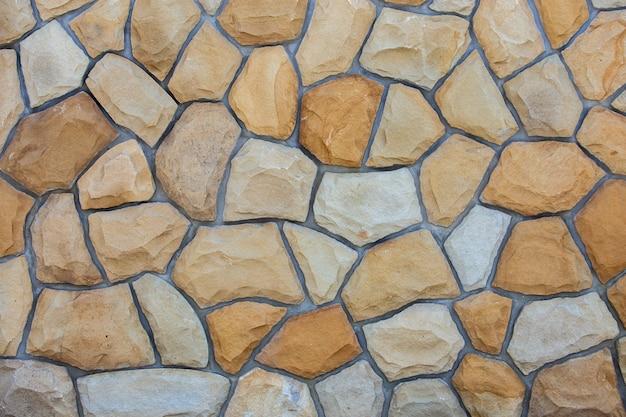 Abstrakte wandfläche aus sandsteinen zur verwendung als hintergrund. Premium Fotos