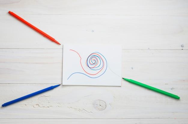 Abstrakte zeichnung auf weißbuch mit rot; grüner und blauer filzstift über schreibtisch aus holz Kostenlose Fotos