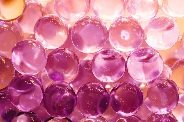 Abstrakter hintergrund mit glänzenden wasserbällen in den farben violett und orange Premium Fotos