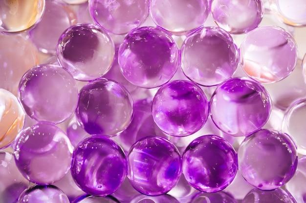 Abstrakter hintergrund mit glänzenden wasserbällen in den violetten und blauen farben Premium Fotos