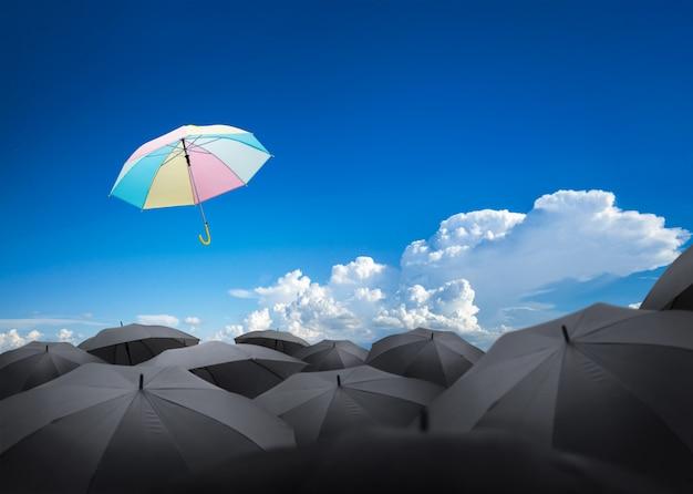 Abstrakter regenschirm, der über viele schwarze regenschirme fliegt Premium Fotos