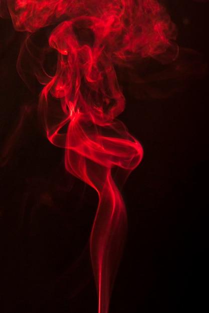Abstrakter roter lockenrauch steigen auf schwarzem hintergrund Kostenlose Fotos
