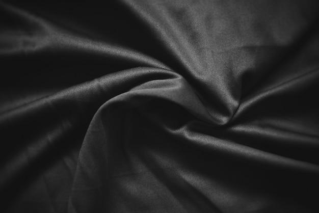 Abstraktes dunkles schwarzes zerknitterte gewebebeschaffenheitshintergrund - glatte elegante schwarze seide, satinluxusstoffwelle Premium Fotos