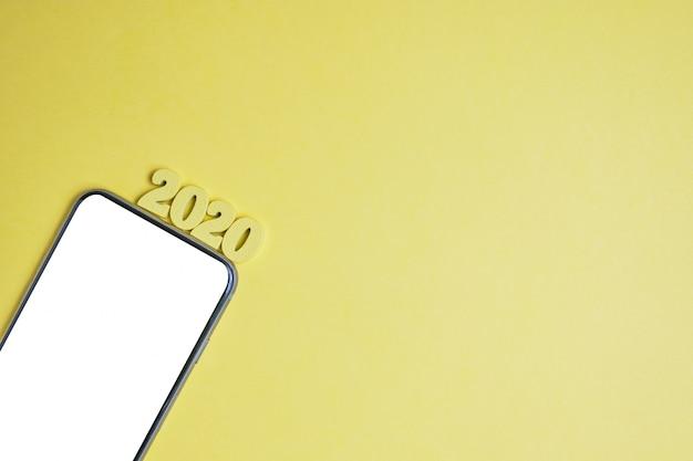 Abstraktes jahr 2020 von holzbuchstaben neben einem telefon in der linken ecke auf gelbem grund. draufsicht. speicherplatz kopieren. Premium Fotos