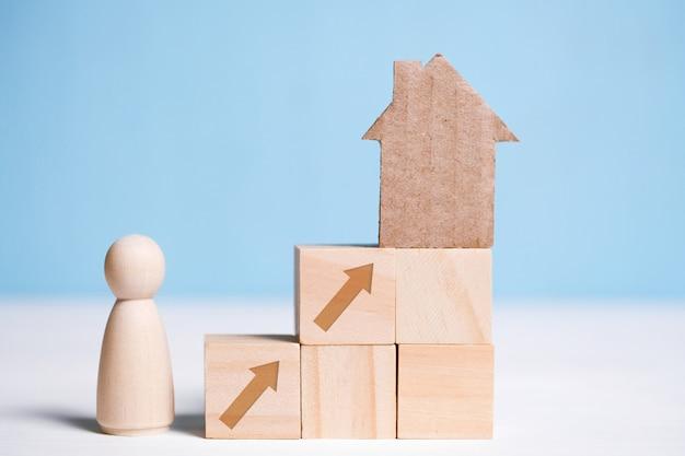 Abstraktes papphaus auf hölzernen würfeln und mann. hauskauf als ziel. Premium Fotos