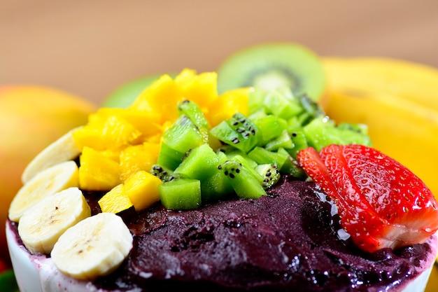 Acai-schüssel mit obstsalat-bananen-mango-kiwi und erdbeere Premium Fotos
