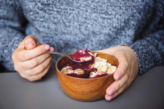 Acai smoothie, granola, samen, frische früchte in einer hölzernen schüssel in den weiblichen händen auf grauer tabelle Premium Fotos