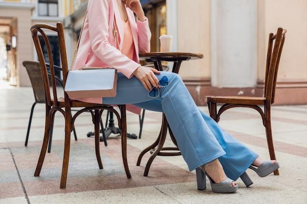 Accessoires der stilvollen frau, die im café sitzt, hosenzangen im vintage-stil, beine in blue jeans, hochhackige schuhe, sonnenbrille, handtasche, rosa und blaue farben, frühlingssommer-modetrend, eleganter stil Kostenlose Fotos