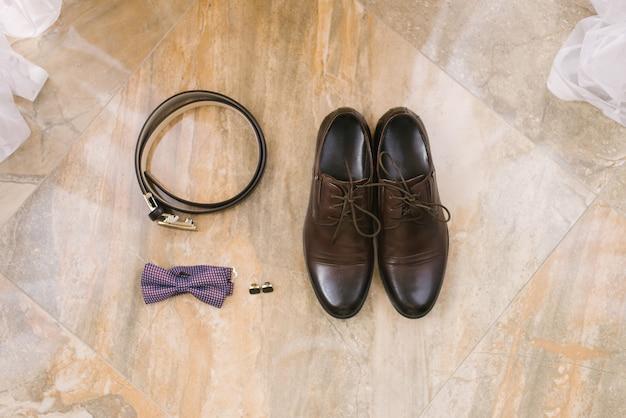 Accessoires für den bräutigam: braune schuhe mit schnürsenkeln, manschettenknöpfen, gürtel und lila fliege auf beige Premium Fotos