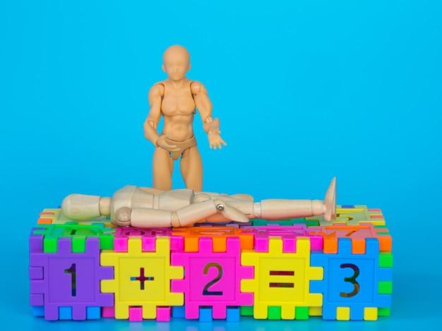 Actionfigur, die in bunten plastikzahlen steht und ein kopfschmerzschauspiel macht Premium Fotos