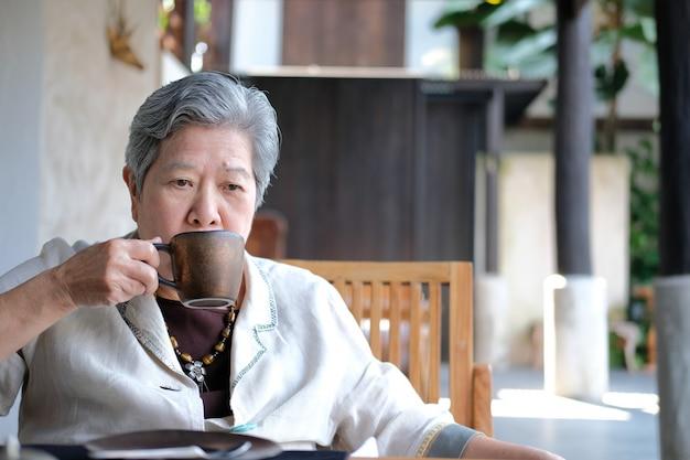 Ältere ältere frau, die kaffee-tee trinkt Premium Fotos