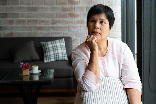 Ältere asien-frau, die seitlich denkt und schaut, denkt und sich wundert Premium Fotos
