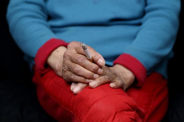 Ältere chinesische frau sitzt und raucht - empowerment-konzept für frauen Kostenlose Fotos