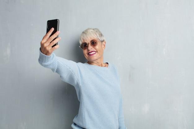 Ältere coole frau mit einem intelligenten telefon gegen schmutzzementwand Premium Fotos