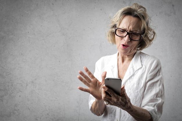 Ältere dame, die einen smartphone verwendet Premium Fotos