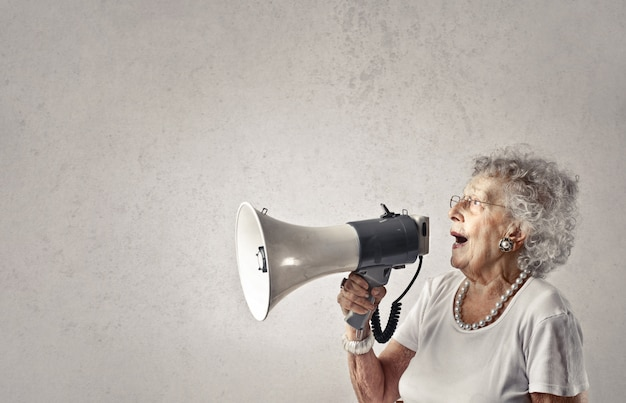 Ältere dame, die in ein megaphon spricht Premium Fotos